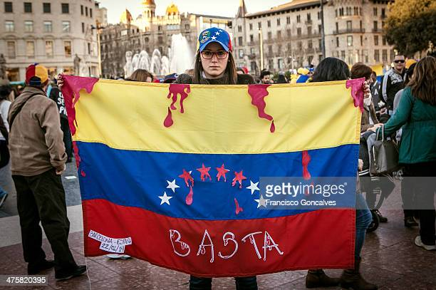 CONTENT] Girl holding a Venezuelan flag with the word enough and blood like stains during a protest against violence and Nicolas Maduro Government in...