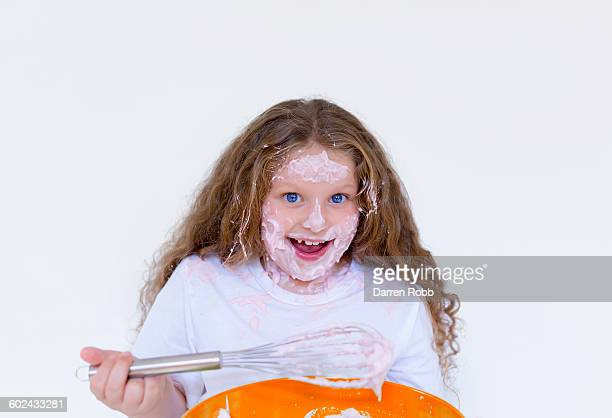 Girl holding a whisk with mixture over her face