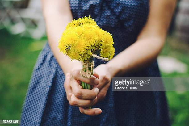 Girl holding a yellow dandelion bouquet