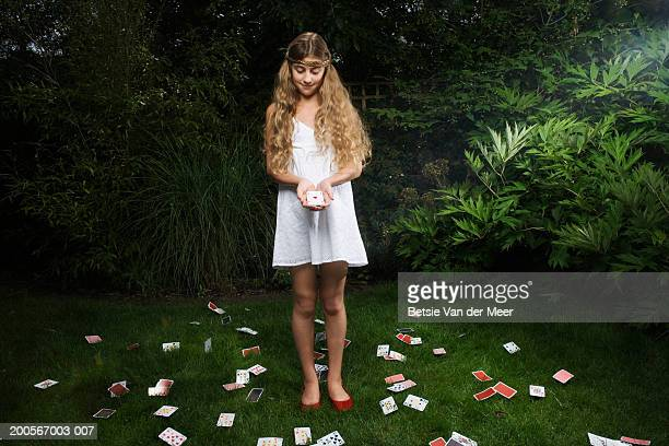 Girl (10-11) holding 'ace of diamonds' card, standing in garden at night