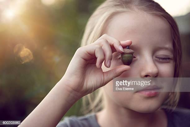 Girl (9-10) holding acorn