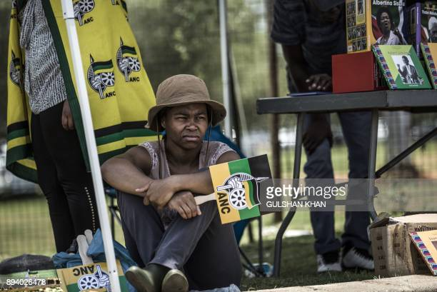 A girl holding an ANC flag sits at an ANC merchandise stall outside the NASREC Expo Centre in Johannesburg on December 17 during the ANC African...