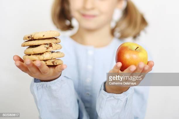 a girl holding an apple and cookies in her hands - alimentação não saudável - fotografias e filmes do acervo
