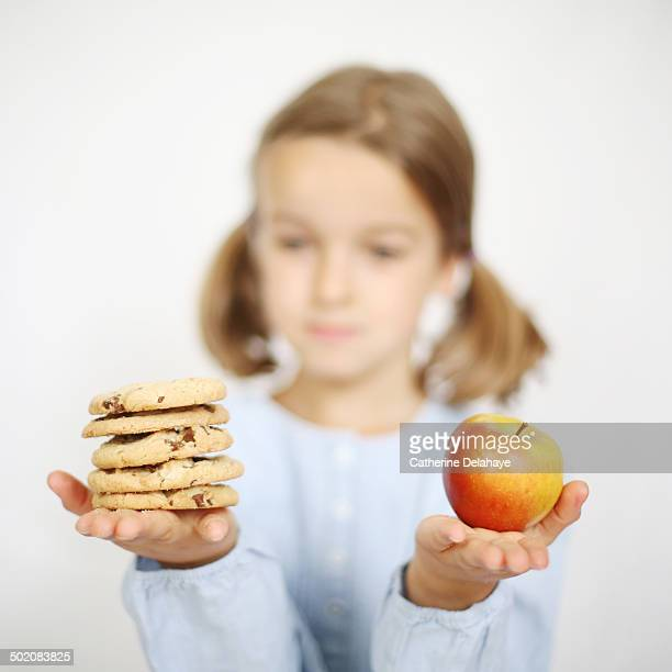 A girl holding an apple and cookies in her hands