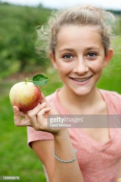 Girl holding an apple in an orchard