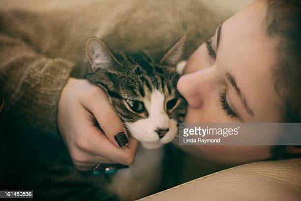 Girl holding and kissing her cat