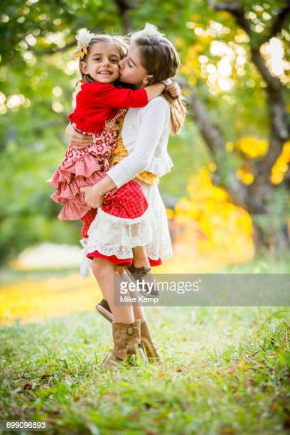 girl holding and kissing sister in cherry orchard - cherry kiss photos et images de collection