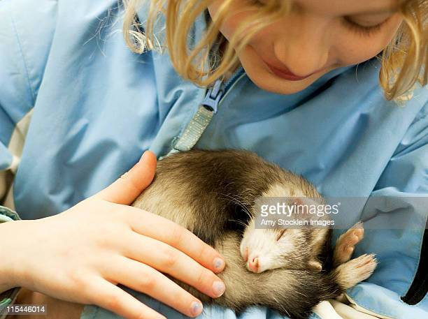 Girl holding and petting sleeping pet