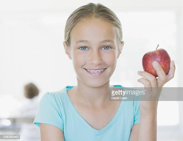 Girl (10-12) holding apple, portrait, smiling