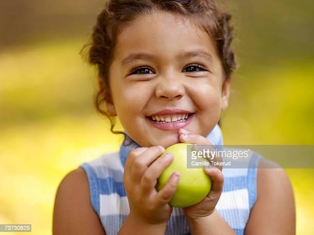 Girl (4-6) holding apple, smiling, close-up, portrait