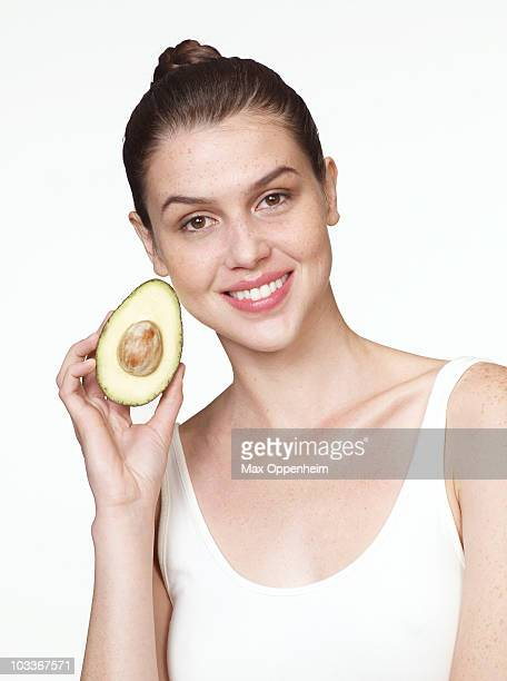 girl holding avocado