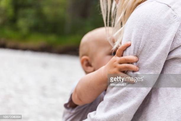 girl holding baby boy brother in the nature - beschützer stock-fotos und bilder