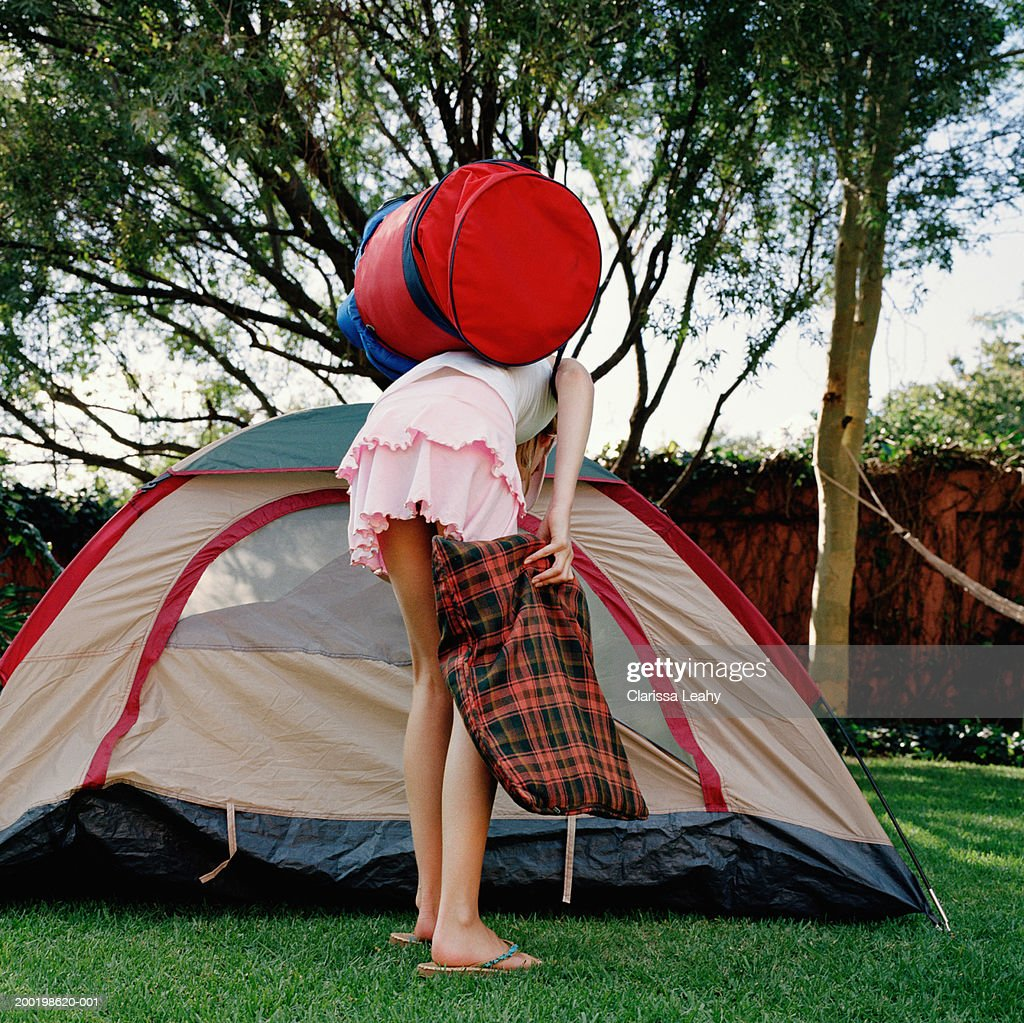 Girl (8-10) holding bags, bending over by opening of tent, rear view : Stock Photo