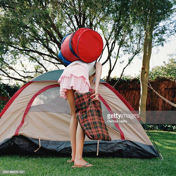 girl (8-10) holding bags, bending over by opening of tent, rear view - little girls bent over stock photos and pictures
