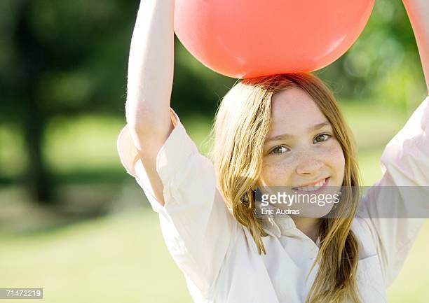 Girl holding ball on head