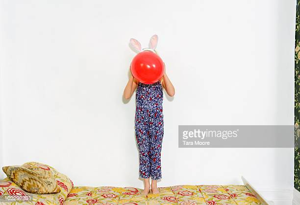 girl holding balloon in front of face