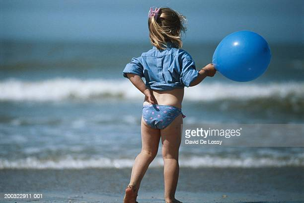 Girl (4-5) holding balloon on beach, rear view