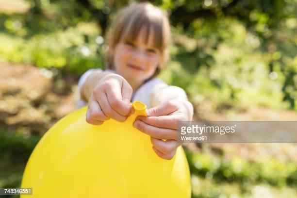 Girl holding balloon on meadow