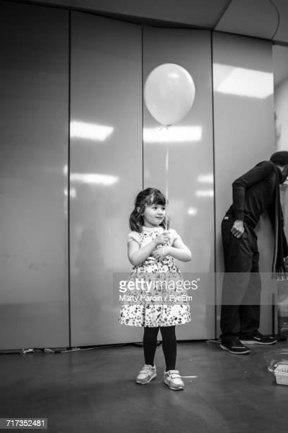 girl holding balloon while standing at home - marty hardin stock photos and pictures