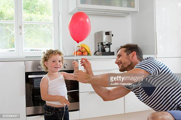Girl holding balloon with father in kitchen