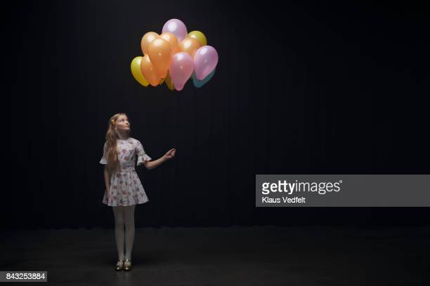 Girl holding balloons and looking at them