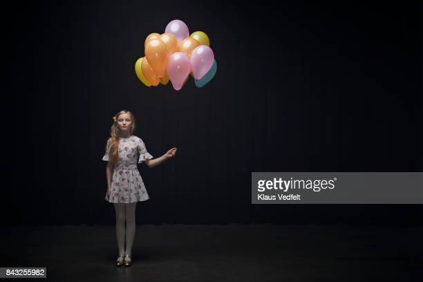 Girl holding balloons and looking in camera