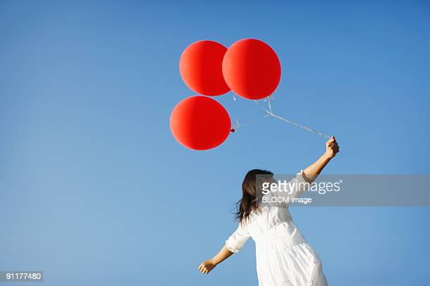 Girl holding balloons, outstretching arms, rear view