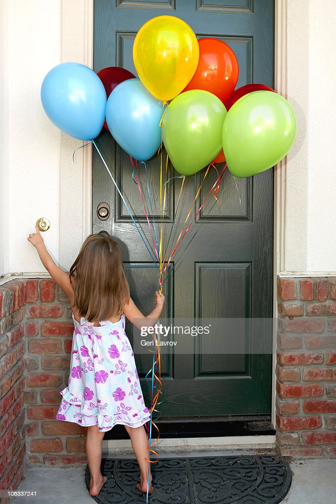 Girl holding balloons ringing a doorbell : Stock Photo