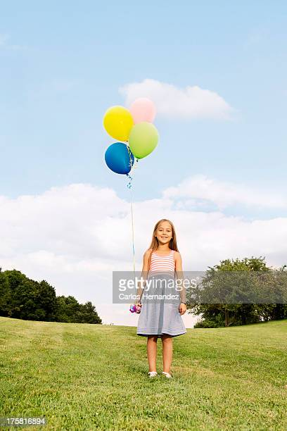 girl holding balloons standing on grass - little girls up skirt stock pictures, royalty-free photos & images