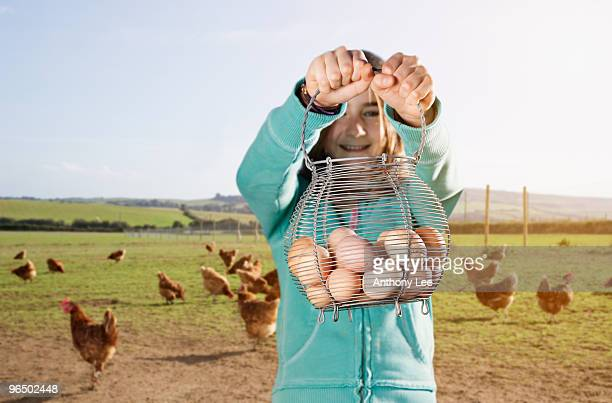 Girl holding basket of eggs near chickens