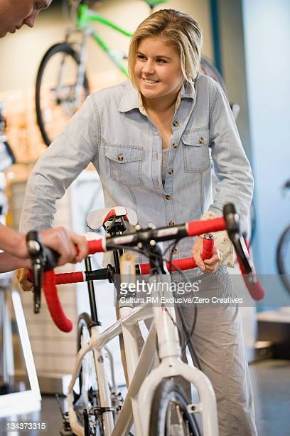 Girl holding bicycle in shop