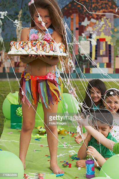 Girl holding birthday cake on a table at a birthday party with her four friends beside her