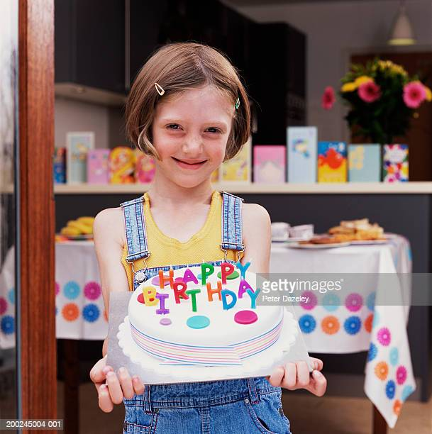 Girl (4-6) holding birthday cake, smiling, portrait