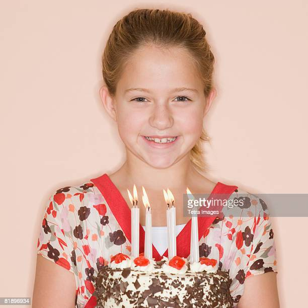 Girl holding birthday cake with lit candles