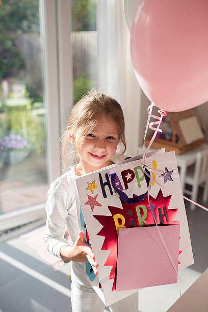 Girl holding birthday present and a balloon