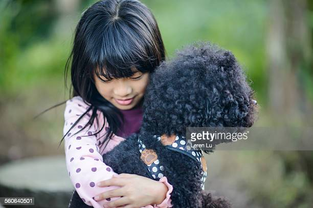 Girl holding black poodle tightly