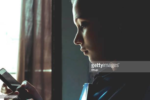 携帯電話で本とテキストメッセージを保持している女の子 - 悲しみ ストックフォトと画像