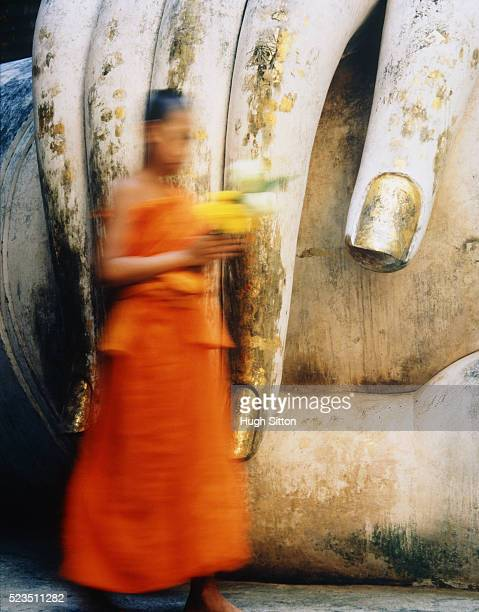 Girl Holding Bouquet by Giant Buddha Statue