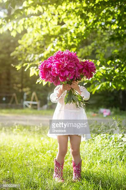 Girl holding bouquet of flowers in backyard