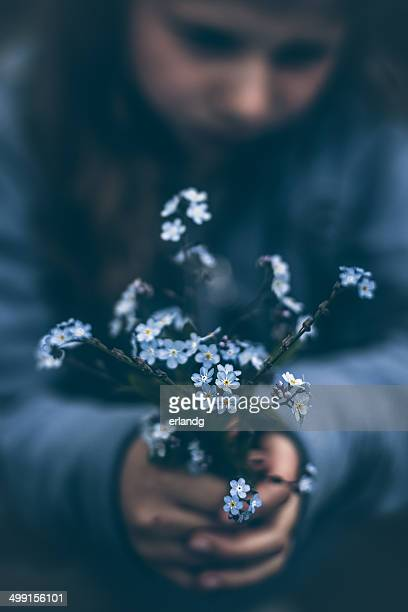 Girl holding bouquet of forget-me-not flowers