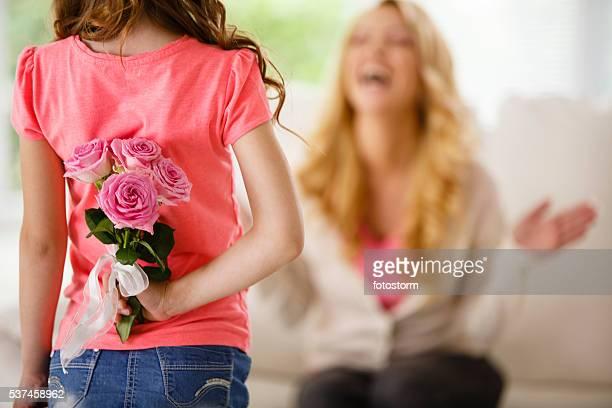Ragazza con bouquet di rose dietro la schiena, sorprendente Madre