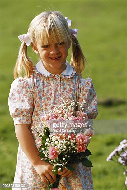 Girl (4-7) holding bouquet outdoors, smiling