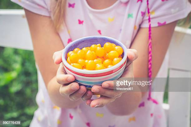 Girl holding bowl with tomberries, yellow mini tomatoes