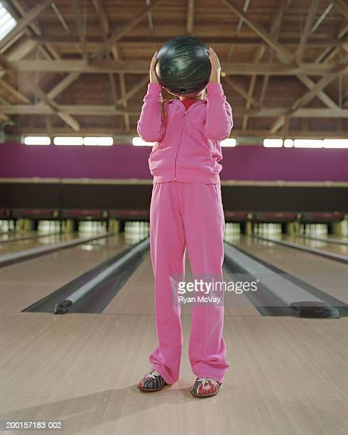 Girl (7-9) holding bowling ball in front of face