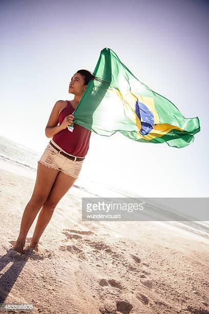 Menina segurando Bandeira Brasileira no vento