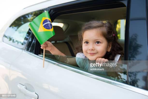 Chica sosteniendo la bandera brasileña.