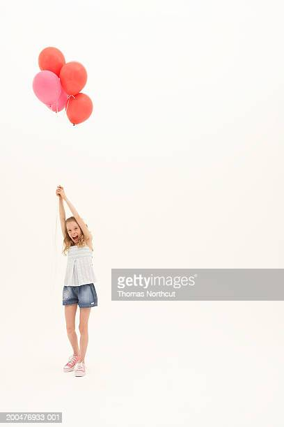 Girl (8-10) holding bunch of balloons, arms raised, portrait