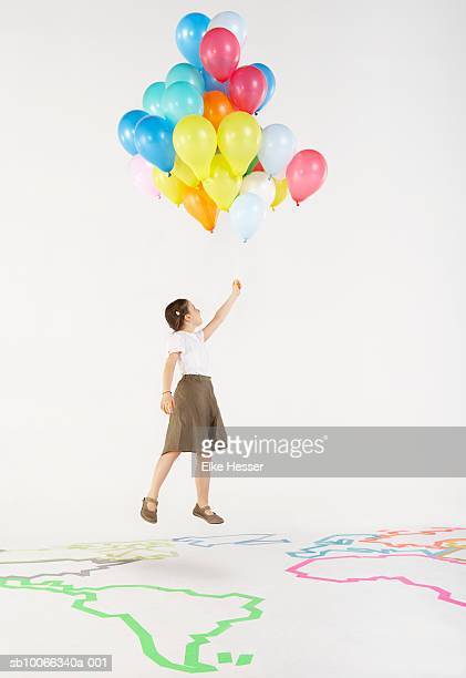 Girl (8-9) holding bunch of balloons on earth map