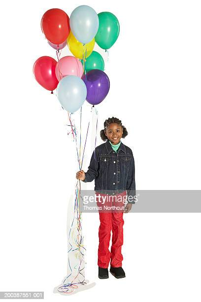 Girl (8-10) holding bunch of balloons, smiling, portrait