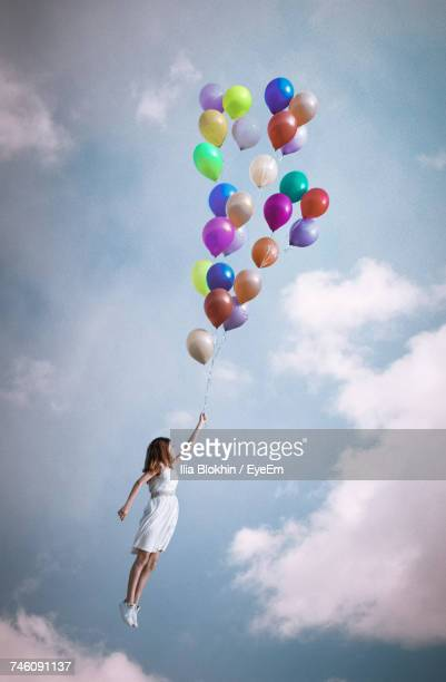 girl holding bunch of balloons while flying at cloudy sky - luftballons himmel stock-fotos und bilder